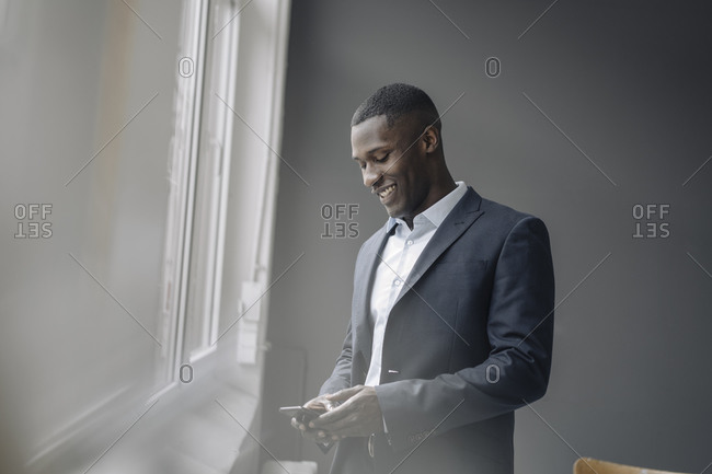 Smiling young businessman standing near window looking at cell phone