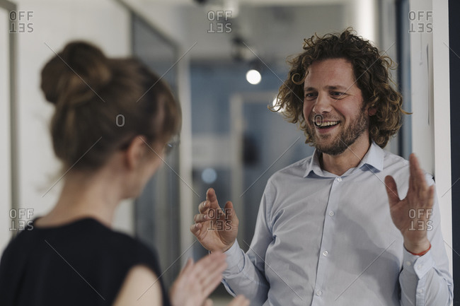 Smiling businessman and businesswoman talking in office