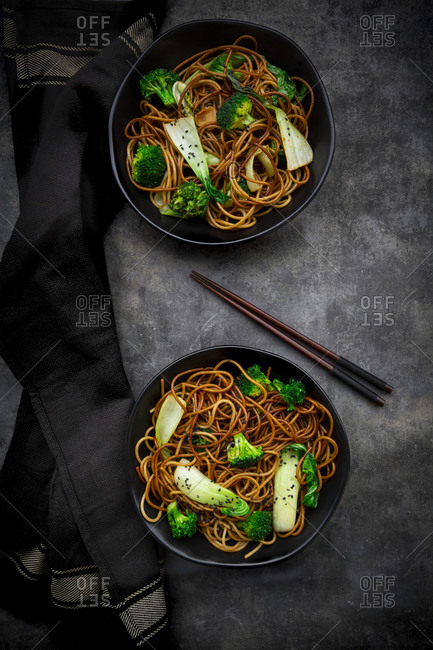 Overhead view of two bowls of soba noodles with pack choi and broccoli- soy sauce and black sesame