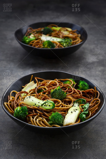Two bowls of soba noodles with pack choi and broccoli- soy sauce and black sesame