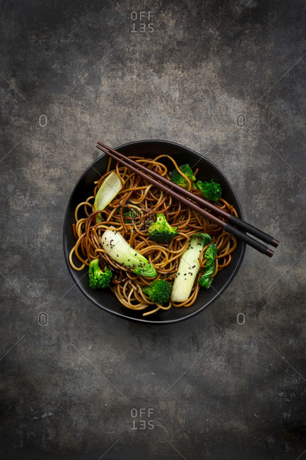Overhead view of bowl of soba noodles with pack choi and broccoli- soy sauce and black sesame