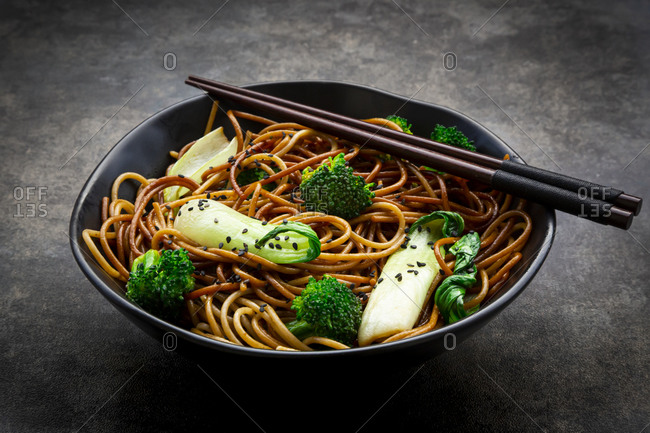 Bowl of soba noodles with pack choi and broccoli- soy sauce and black sesame