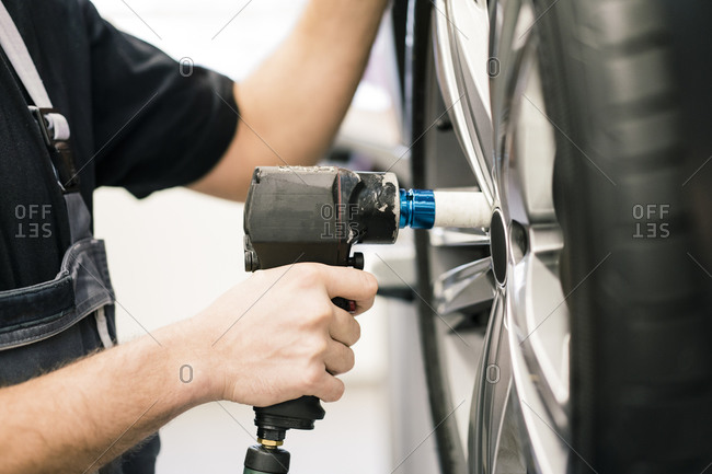 Close-up of car mechanic in a workshop changing tire