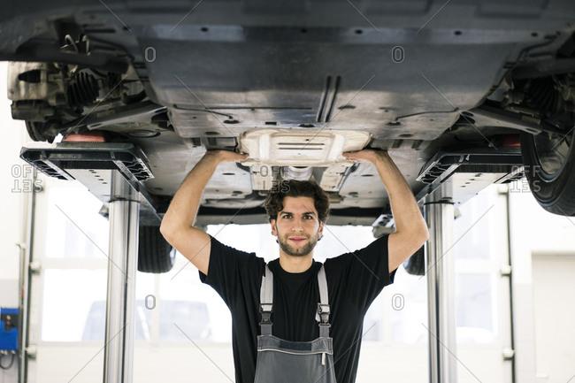 Portrait of a confident car mechanic in a workshop