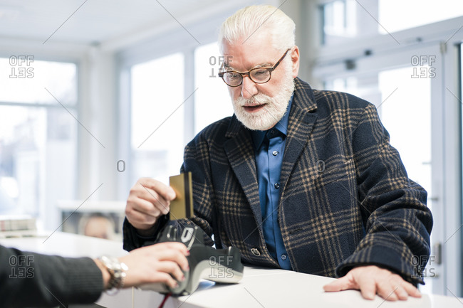 Senior man paying with credit card at the counter of a shop