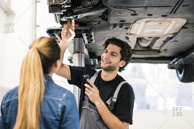 Car mechanic talking to client in workshop
