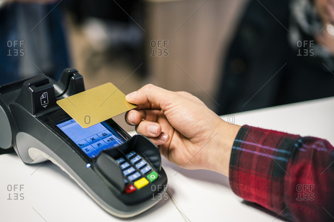 Close-up of man paying contactless with credit card