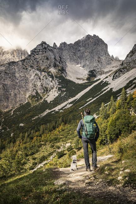 Woman on a hiking trip at Wilder Kaiser enjoying the view- Kaiser mountains- Tyrol- Austria
