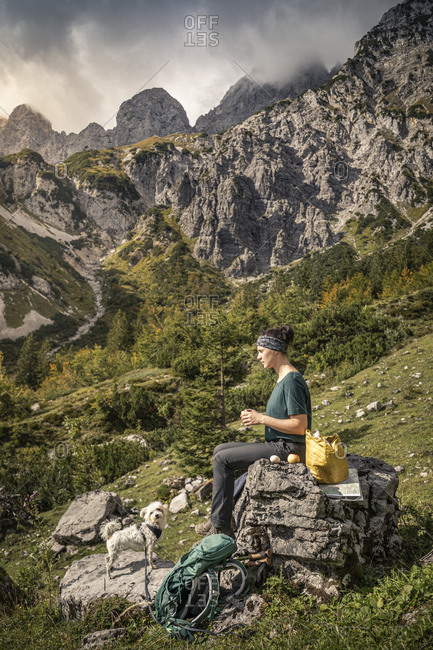 Woman with dog on a hiking trip at Wilder Kaiser having a break- Kaiser mountains- Tyrol- Austria