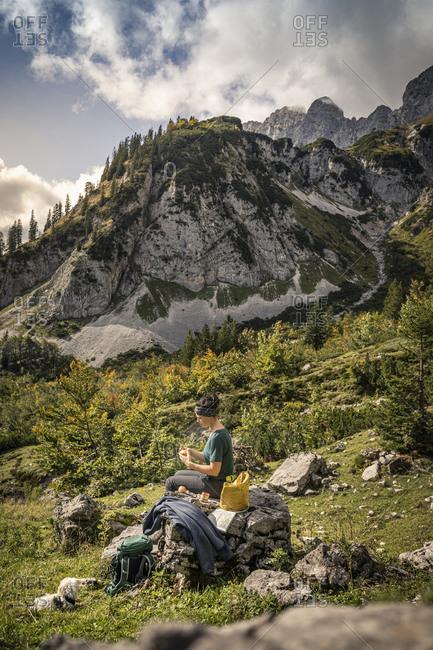 Woman with dog on a hiking trip at Wilder Kaiser having a break- Kaiser mountains- Tyrol- Austria