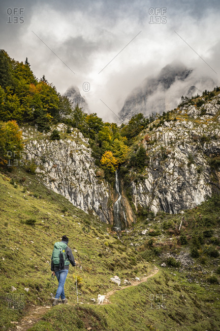 Woman with dog hiking in Kaiser mountains- Tyrol- Austria