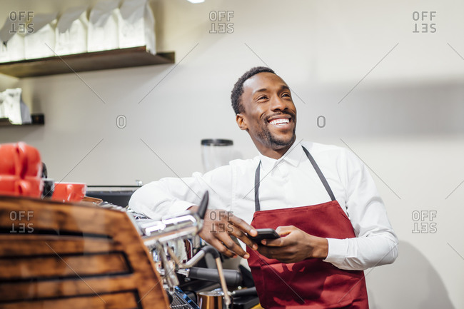 Happy barista holding cell phone in a coffee shop