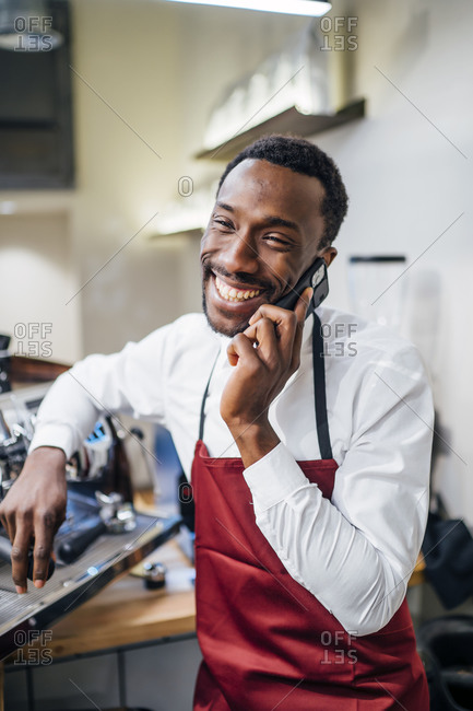 Happy barista on the phone in a coffee shop