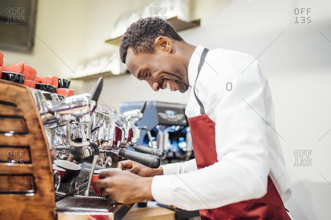 Smiling barista preparing a coffee in a coffee shop