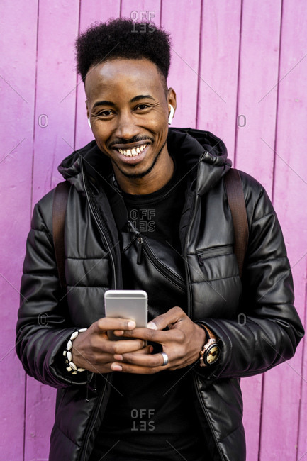 Portrait of smiling man with smartphone and wireless earphones outdoors