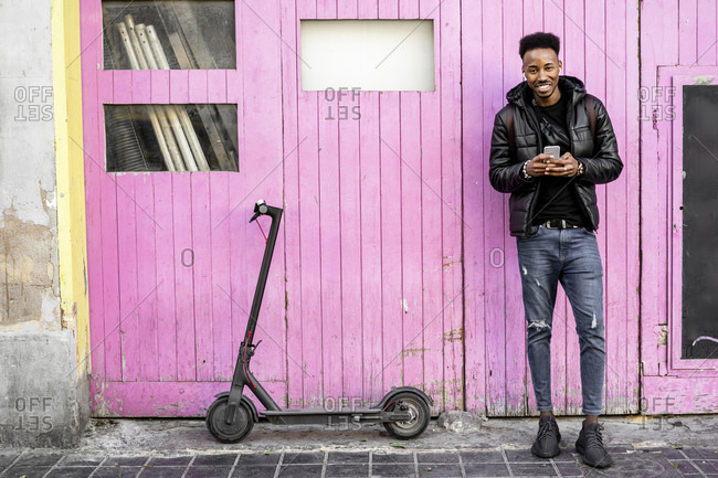 Portrait of smiling man with smartphone and e-scooter outdoors