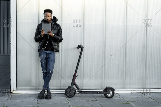 Man with headphones- tablet and e-scooter outdoors