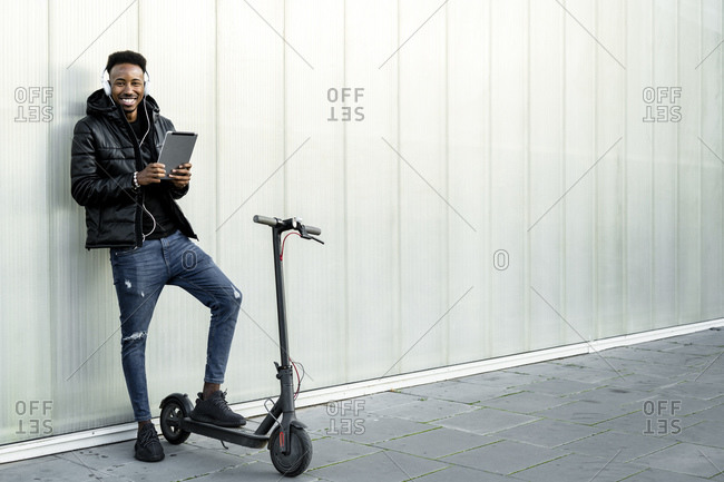 Portrait of happy man with headphones- tablet and e-scooter outdoors