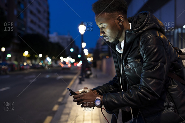 Man in the city at night with smartphone and e-scooter