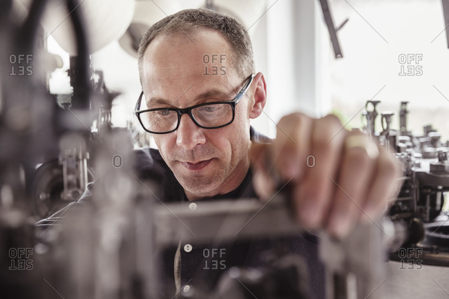Portrait of focused man working at a machine in a textile factory
