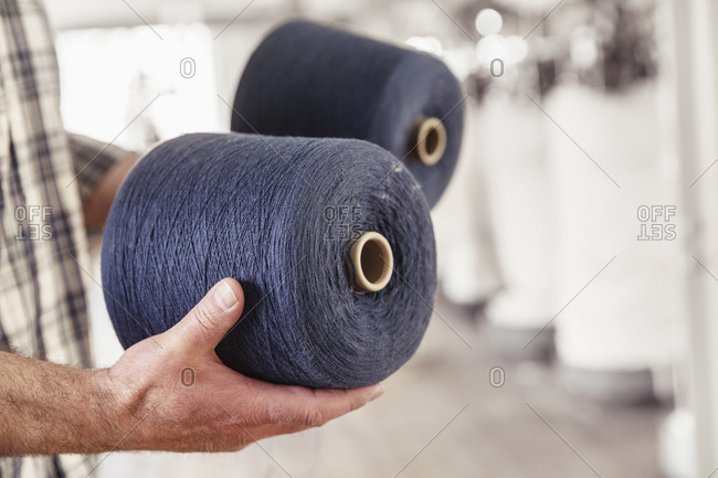 Close-up of man holding cotton reels in a textile factory