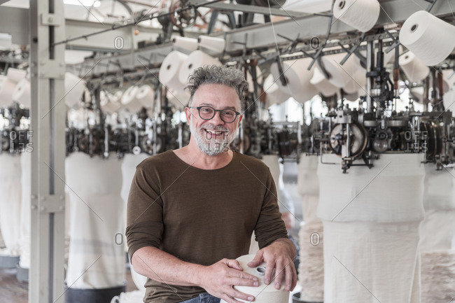 Portrait of a happy mature man in a textile factory