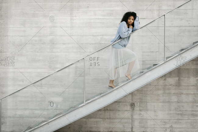 Beautiful young woman standing on stairs outdoors