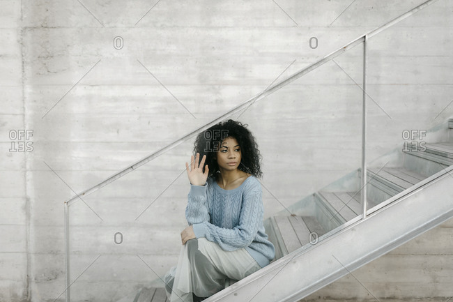 Beautiful young woman sitting on stairs behind a glass pane
