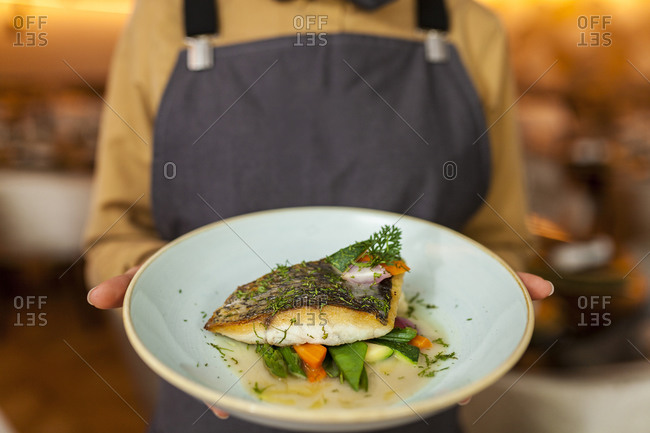 Waitress serving healthy fish and veggies