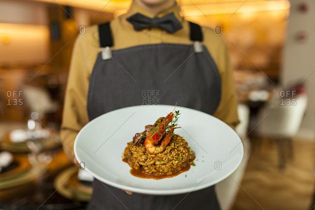 Waitress serving paella on white plate