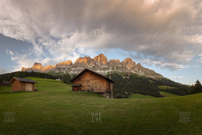 The Catinaccio mountain range at the sunset with some chalet on a green meadow and cloudy orange sky, dolomites, South Tyrol, Italy, Europe