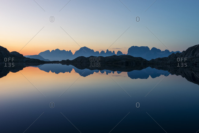 Brenta mountain range skyline at the dusk reflected on the Lago Nero of Cornisello, Nambrone valley, Madonna di Campiglio, Trentino Alto Adige, dolomites, Italy, Europe