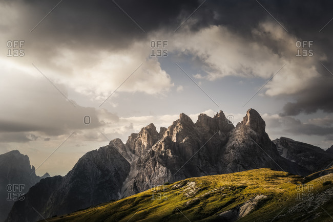 Mount Rudo in the Sesto Dolomites, framed by storm clouds and alpine meadows, South Tyrol, Italy, Europe