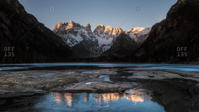 Cristallo mount during sunrise is reflected in the frozen Landro lake, South Tyrol, dolomites, Italy, Europe