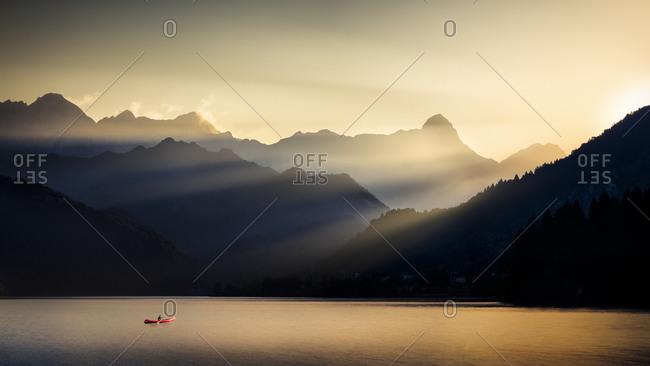 A canoeist crosses the Barcis lake at sunset, Dolomiti Friulane natural park, dolomites, Friuli Venezia Giulia, Italy, Europe
