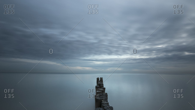 A wooden pile trail points towards the horizon between sky and sea, Bibione, Adriatic sea, Veneto, Italy, Europe