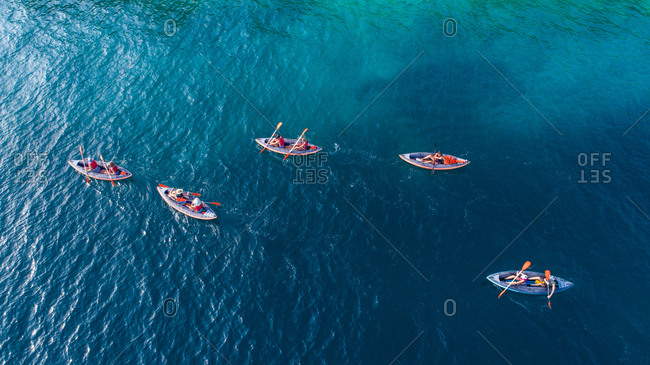 August 13, 2019: Aerial view of group of kayakers paddling in crystal clear Adriatic sea in Dalmatia, Croatia.