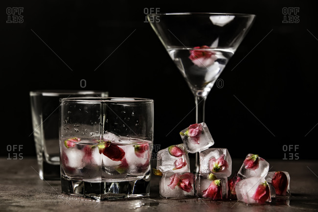 Vodka with french roses in ice in a glass