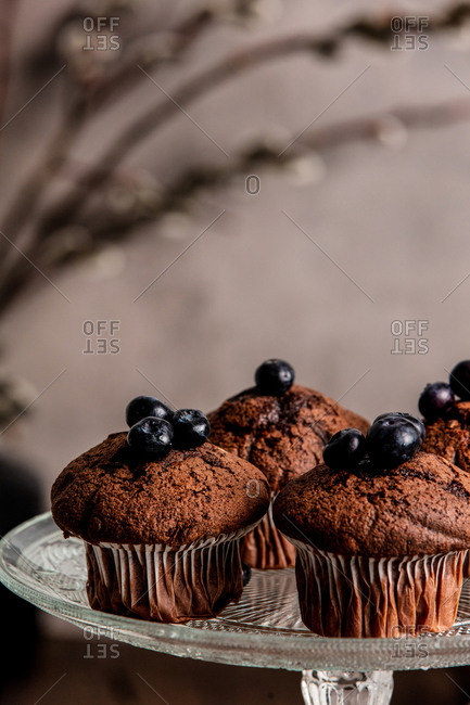 Chocolate cupcakes with blueberries and raspberries on wooden table