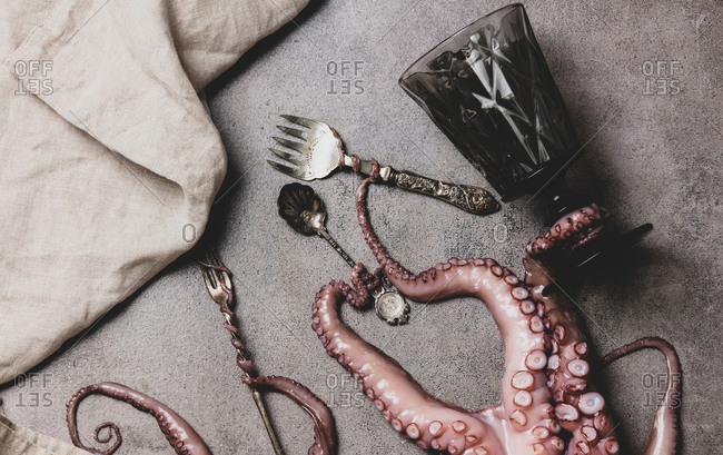 octopus holds forks with tentacles on a table