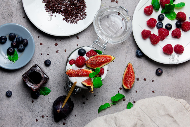 Ice cream with raspberries and blueberries and common fig on a table