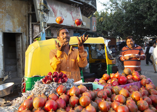 New Delhi, India - March 2, 2015: Fruit seller throws pomegranates in the air.