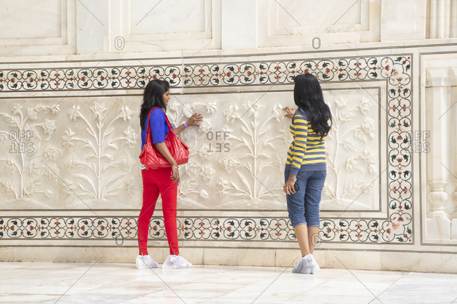 Agra, India - March 2, 2015: Two female Indian tourists admire the marble relief of the Taj Mahal.