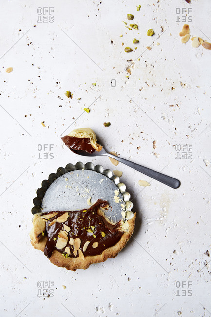 Half eaten chocolate ganache tart with a spoonful on a white background,