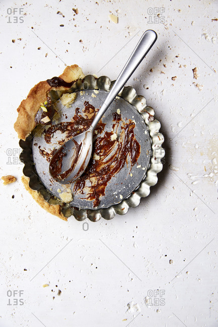 Leftovers of decadent chocolate ganache tartlet in baking tin on a white background,