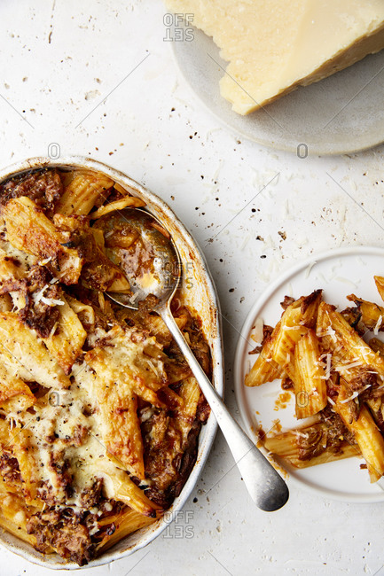 A serving bowl of baked ragu and penne pasta with a silver spoon and parmesan on a white countertop,