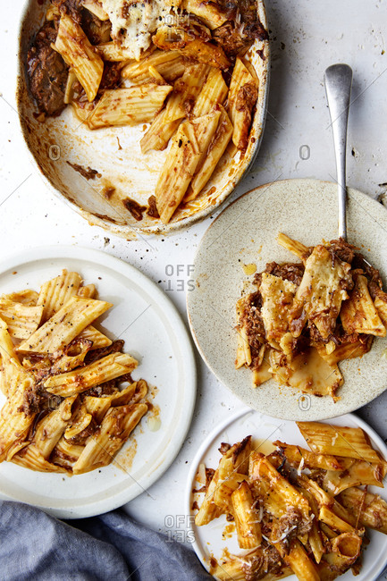 A serving bowl of baked ragu and penne pasta with a some plates served up on the side on a white countertop,