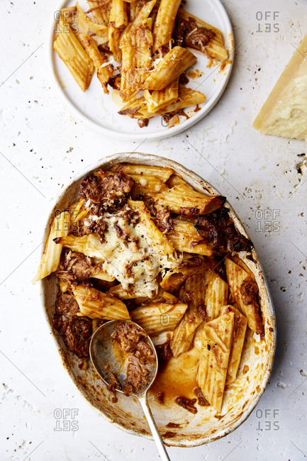 A serving bowl of baked ragu and penne pasta with a plate served on the side on a white countertop,