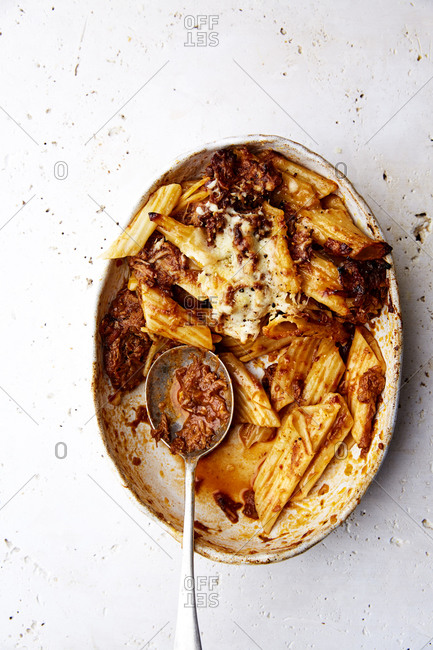 A serving bowl of baked ragu and penne pasta with a silver spoon on a white countertop,