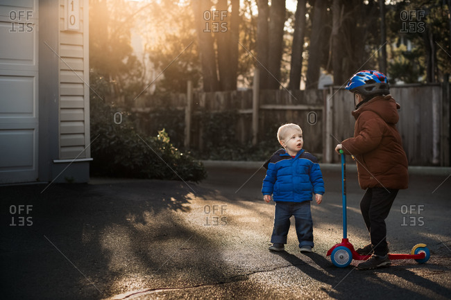 Boys playing in the driveway at sunset